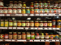 Salsa Jars Lined Up on Supermarket Shelves. Salsas of all varieties are lined up, and for sale, on shelves of a specialty supermarket stock image