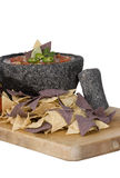 Salsa in Molcajete with blue chips. Homemade salsa in traditional mexican molcajete mortar with blue and white organic corn chips royalty free stock photos