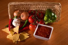 Salsa, nachos, ingredients. Nacho chips, salsa dip and its ingredients in a basket Royalty Free Stock Image