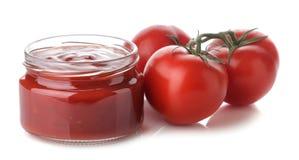 Salsa roja en un tarro y los ingredientes frescos, tomates en un fondo aislado blanco Salsa de tomate hecha en casa ketchup foto de archivo libre de regalías