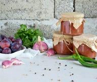 Salsa sabrosa de ciruelos, del ajo, del cilantro, del eneldo y del pimiento picante rojos Tkemali georgiano en el fondo blanco Ot fotos de archivo libres de regalías