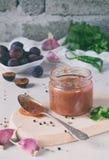 Salsa sabrosa de ciruelos, del ajo, del cilantro, del eneldo y del pimiento picante rojos Tkemali georgiano en el fondo blanco Ot imagenes de archivo