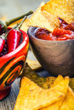 Salsa with tortilla chips and chilli peppers.Concept Royalty Free Stock Photo