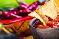 Salsa with tortilla chips and chilli peppers.Concept Stock Photo