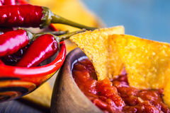 Salsa with tortilla chips and chilli peppers.Concept Royalty Free Stock Photography