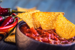 Salsa with tortilla chips and chilli peppers.Concept Stock Photos