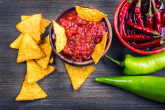 Salsa with tortilla chips and chilli peppers.Concept Royalty Free Stock Images
