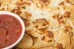 Salsa with tortilla chips. Covered with a thick layer of mozzarella cheese Royalty Free Stock Photography