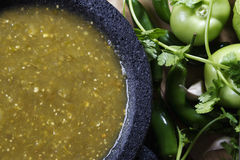 Salsa verde. Stock image of mexican salsa verde on mortar and pestle with ingredients stock photography