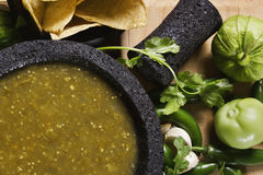 Salsa verde. Stock image of mexican salsa verde on mortar and pestle with ingredients stock photos