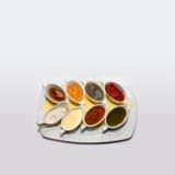 Salsas clásicas en cazos en la placa gris Sazone la mostaza del tomate con pimienta del pesto del aioli del queso verde del chimi Imagen de archivo