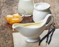 Salsera con la salsa y los ingredientes de la vainilla Imagenes de archivo