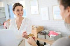 Salseswoman в магазине одежды получая внутри приобретение наличными ее клиента Стоковая Фотография