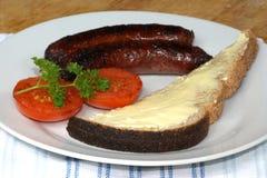 Salsicce di maiale cotte, pane tostato con il pomodoro Fotografia Stock