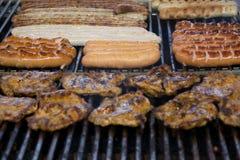 Salsicce e bistecche di maiale tedesche sulla griglia del barbecue fotografia stock