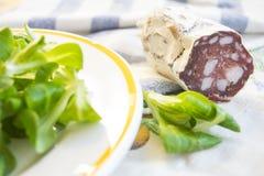 Salsiccia affumicata del salame vicino al salade della lattuga Fotografie Stock Libere da Diritti