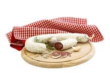 Salsiccia asciutta curata sulla scheda di legno isolata su briciolo Immagine Stock