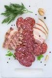 Salsiccia, bacon e verdi affumicati su un fondo bianco Immagine Stock