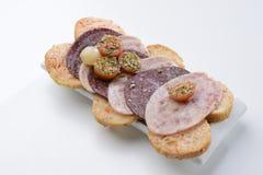 Salsiccia in bianco e nero su un letto del pane del pomodoro Immagine Stock