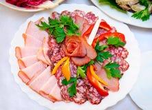 Salsiccia, carne e pepe su una zolla bianca Fotografie Stock Libere da Diritti