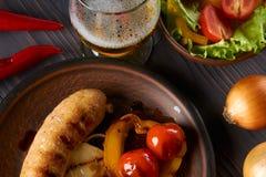 Salsiccia del pollo con le verdure e la birra leggera su un piatto dell'argilla immagini stock