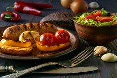 Salsiccia del pollo con le verdure su un piatto dell'argilla immagini stock