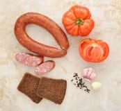 Salsiccia di Cracovia, pomodori e pane nero immagine stock libera da diritti
