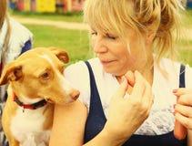 Salsiccia di elasticità della donna al cane fotografia stock libera da diritti