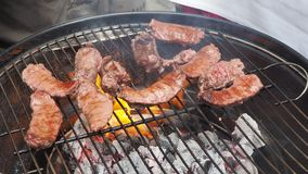 Salsiccia di maiale succosa arrostita cucinata sopra i carboni su un barbecue stock footage