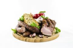 Salsiccia e bacon con le verdure sul bordo di legno Fotografia Stock