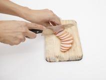 Salsiccia e coltello su fondo bianco Immagine Stock