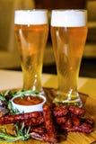 Salsiccia e costole di carne di maiale fritte con birra Fotografia Stock