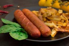 Salsiccia e patate fritte Vecchio fondo nero Primo piano Vista superiore Immagine Stock
