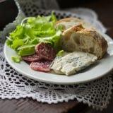 Salsiccia, formaggio di Gorgonzola e pane italiani di ciabatta su un piatto bianco Fotografia Stock