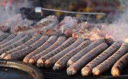 Salsiccia fresca e hot dog grigliati all'aperto su una griglia del gas Salsiccie su un barbecue Alimenti a rapida preparazione fu Fotografia Stock Libera da Diritti