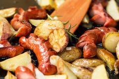 Salsiccia fritta con le patate, l'aglio e le cipolle fotografia stock libera da diritti
