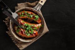 Salsiccia fritta su una vecchia pentola Fotografie Stock