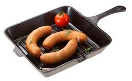 Salsiccia per grigliare nella pentola Isolato su bianco Fotografie Stock Libere da Diritti