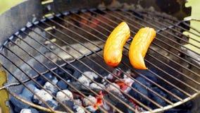 Salsiccia succosa sulla griglia calda con le tenaglie durante il barbecue di estate stock footage