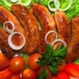 Salsiccia sulla griglia con prezzemolo, i pomodori e le cipolle Fotografia Stock