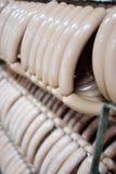 Salsiccie affumicate Mouthwatering sui precedenti di una fabbrica della carne Fotografia Stock