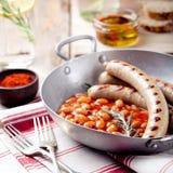 Salsiccie arrostite con i fagioli in salsa al pomodoro Immagine Stock