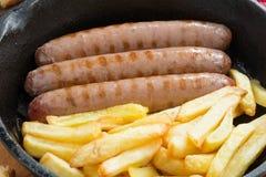 Salsiccie arrostite con le patate fritte in una padella, primo piano Immagine Stock Libera da Diritti