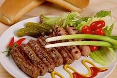 Salsiccie arrostite con le verdure su un piatto bianco Fotografia Stock
