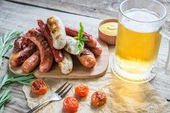 Salsiccie arrostite con vetro di birra Fotografia Stock