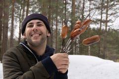 Salsiccie arrostite dell'uomo sopra firecamp fotografie stock libere da diritti