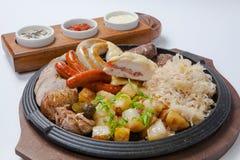 Salsiccie arrostite e patate sulla cottura della pentola Fotografia Stock