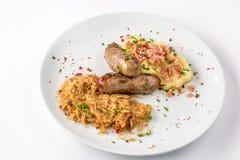 Salsiccie arrostite, patate e cavolo brasato sulla vista bianca del primo piano del piatto da sopra Immagini Stock