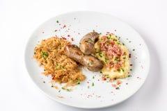 Salsiccie arrostite, patate e cavolo brasato sulla vista bianca del primo piano del piatto da sopra Fotografie Stock Libere da Diritti