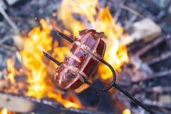 Salsiccie che cuociono sopra il fuoco del campo Partito con gli amici immagine stock libera da diritti